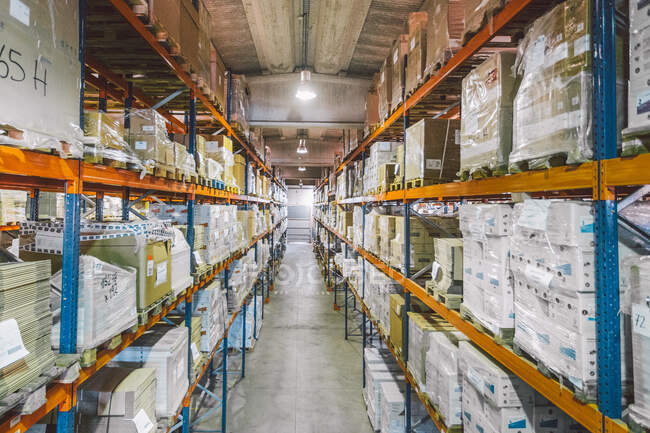From above of empty narrow passage between big metal shelves with different packages and boxes in warehouse — Stock Photo