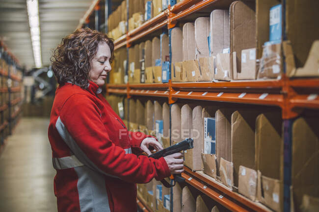 Side view of content female employee in red uniform with tool in hands standing near selves with boxes — Stock Photo
