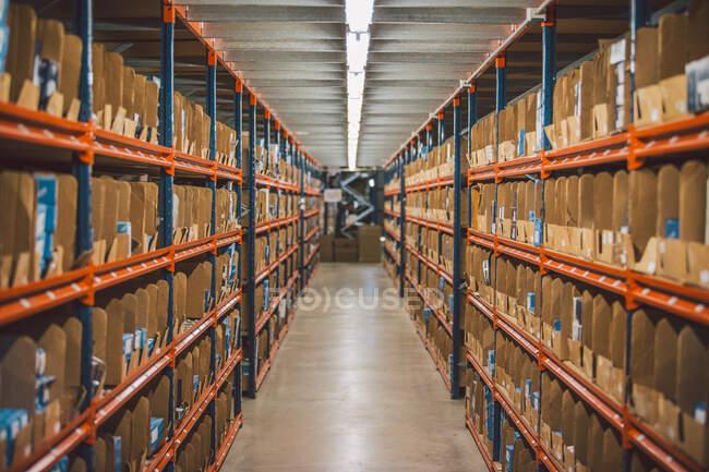Сверху пустой узкий проход между большими металлическими полками с различными упаковками и коробками на складе — стоковое фото