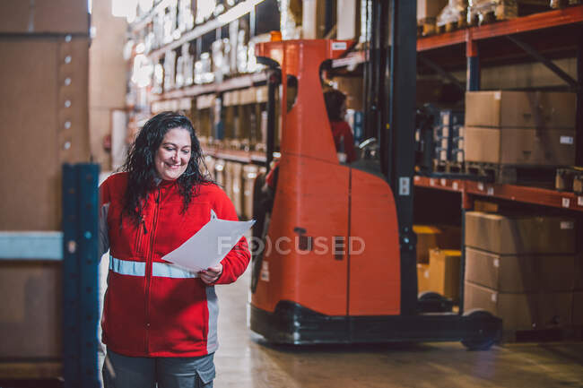 Satisfied black haired woman in red uniform smiling while reading document during work in big storage with packages — Stock Photo