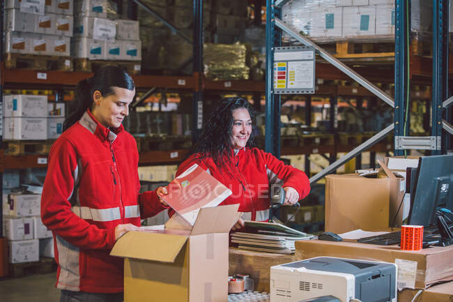 Pleased female employees in red uniform searching packages and collecting parcels in big modern warehouse — Stock Photo