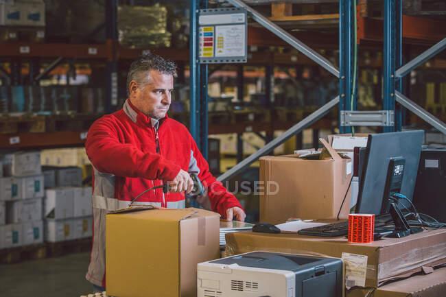 Empleado de hombre en paquetes de escaneo uniformes rojos y paquetes de recolección en un gran almacén moderno - foto de stock