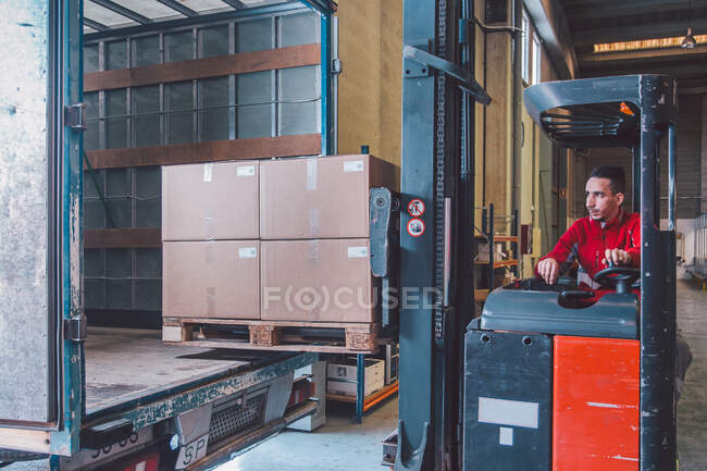Male driver of forklift truck during shipment packages from big truck in modern warehouse — Stock Photo