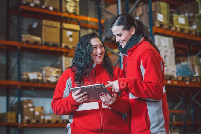 Von unten lächeln junge Frauen in roter Uniform bei der Arbeit im modernen Lager mit dem digitalen Tablet — Stockfoto