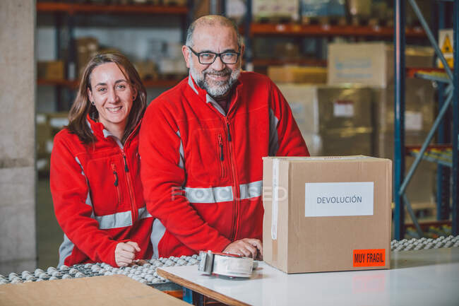 Satisfied male and female employees of warehouse in red uniforms smiling and looking at camera with package on table — Stock Photo