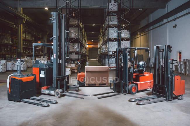Moderne verschiedene Modelle von Gabelstaplern im großen Lager für den Arbeitstag vorbereitet — Stockfoto