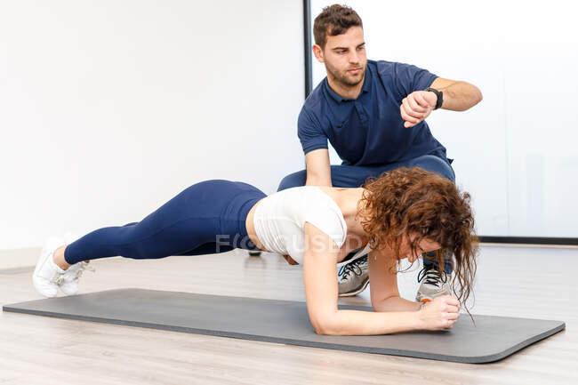 Señora haciendo ejercicio de tablón con instructor personal en el gimnasio - foto de stock