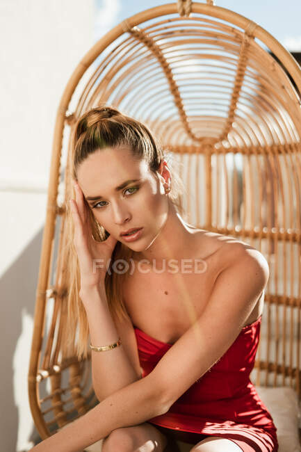 Sensual blonde haired beautiful female model with golden earrings in red stylish dress sitting on hanging chair at outdoors terrace in sunlight — Stock Photo