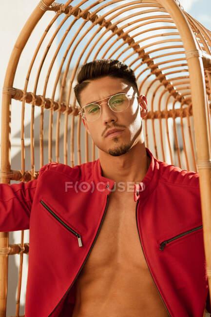 Uomo bello serio con acconciatura elegante in occhiali alla moda e giacca rossa seduta sulla sedia appesa e guardando la fotocamera — Foto stock