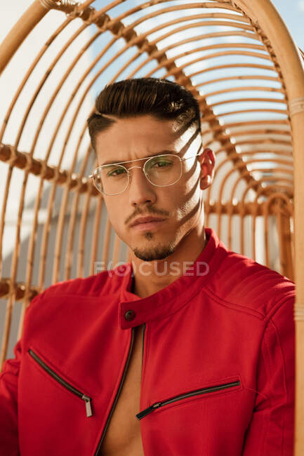 Serious handsome man with stylish hairdo in trendy eyeglasses and red jacket sitting on hanging chair and looking at camera — Stock Photo