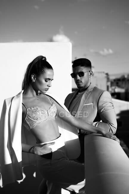 Чорно-білий погляд на безпристрасну пару в модному костюмі і одяг, що стоїть на балконі і озирається геть — стокове фото