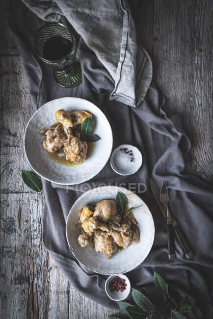 Draufsicht auf geschmorte Hühnertrommeln mit Brühe in weißer Keramikschüssel, dekoriert mit Grün auf einem Tisch mit Gewürzen und Getränken — Stockfoto
