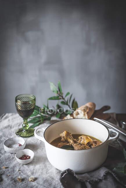 Сверху тушеные куриные барабанные палочки с бульоном в белой керамической миске украшены зеленью на столе со специями хлеба и напитков — стоковое фото