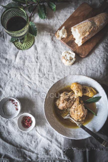 Верхній вид тушкованих курячих барабанних паличок з бульйоном у білій керамічній мисці, прикрашеній зеленню на столі з спеціями, хлібом і напоєм. — стокове фото