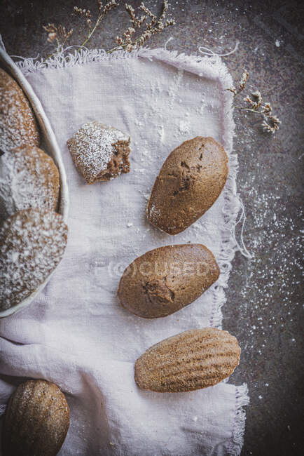 Dall'alto la vista di biscotti al forno marroni in forma di conchiglia su tovaglia bianca — Foto stock