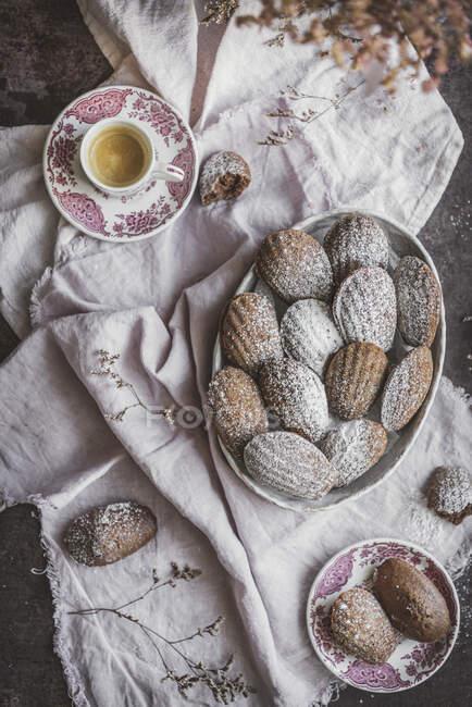 Зверху на стіл з чашкою чаю подають солодке печиво з порошком. — стокове фото