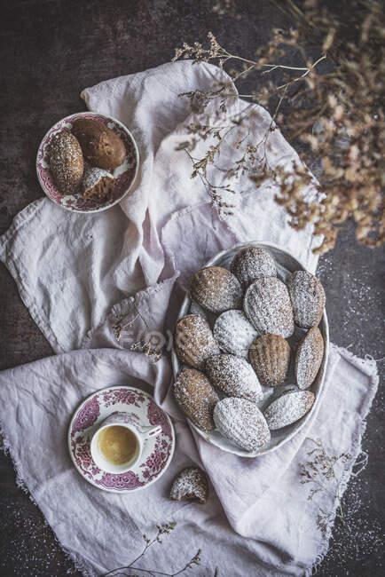 Dall'alto vista di stuzzicanti biscotti dolci serviti con polvere in polvere sul tavolo con tazza di tè — Foto stock