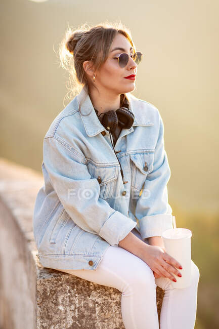 Side view of young woman in casual wear with sunglasses resting on rocky fence with beverage and listening music with headphones — Stock Photo