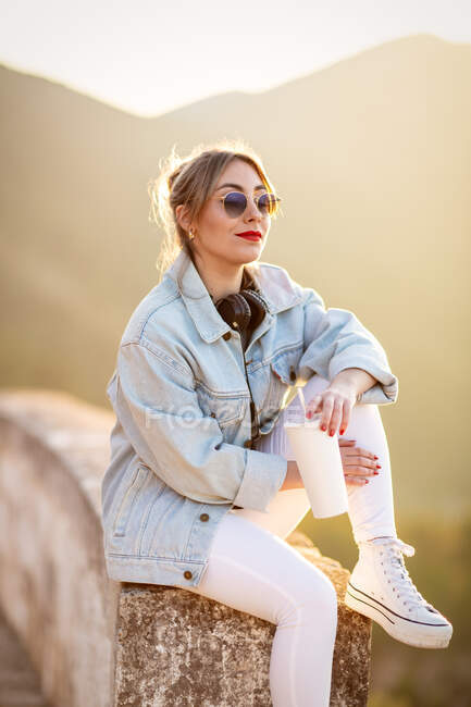 Satisfied blond haired lady in trendy sunglasses and casual wear sitting on rocky fence and looking away in sunlight on blurred background — Stock Photo