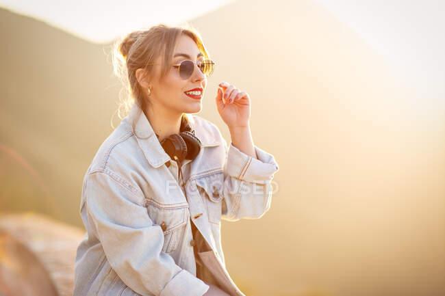 Giovane donna allegra con occhiali da sole in abito casual alla moda sorridente e guardando altrove nella giornata di sole — Foto stock