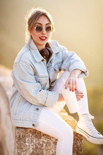Satisfied blond haired lady in trendy sunglasses and casual wear sitting on rocky fence and looking at camera in sunlight on blurred background — Stock Photo