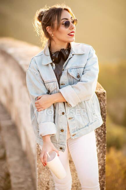 Giovane donna in abbigliamento casual con occhiali da sole poggiata su recinzione rocciosa con bevanda e musica d'ascolto con cuffie — Foto stock
