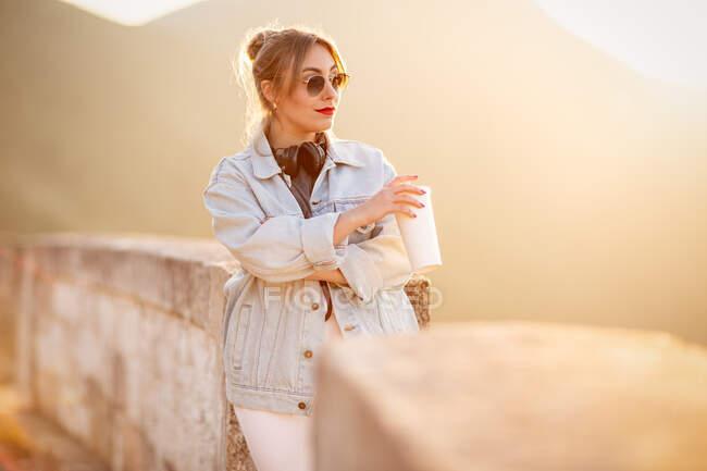 Vista laterale di signora premurosa in abbigliamento casual poggiata su recinzione rocciosa con bevanda e musica d'ascolto con cuffie — Foto stock