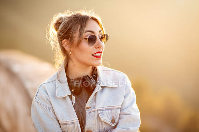 Joyful young woman with sunglasses in trendy casual outfit smiling and looking away on sunny day — Stock Photo