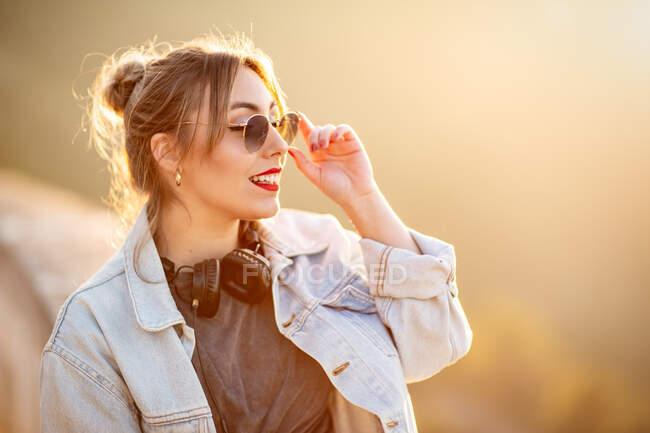 Радостная молодая женщина в солнечных очках в модном повседневном наряде улыбается и смотрит в сторону в солнечный день — стоковое фото