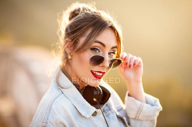 Радостная молодая женщина в солнечных очках в модном повседневном наряде улыбается и смотрит в камеру в солнечный день — стоковое фото