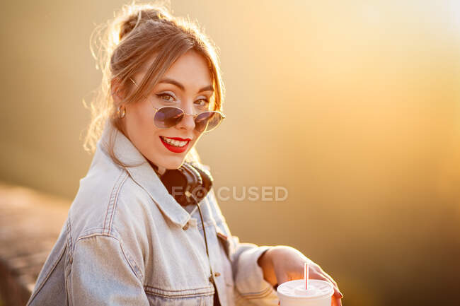 Joyful young woman with sunglasses in trendy casual outfit smiling and looking at camera on sunny day — Stock Photo