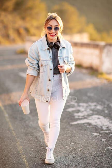 Joyeuse femme blonde aux cheveux en tenue élégante et lunettes de soleil marchant avec des boissons et souriant à la caméra sur fond flou — Photo de stock