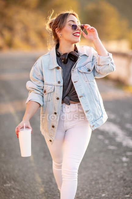 Fröhliche blondhaarige Frau in stylischem Outfit und Sonnenbrille, die mit Getränken spaziert und auf verschwommenem Hintergrund lächelt — Stockfoto