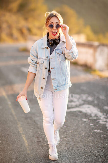 Gioiosa donna dai capelli biondi in abito elegante e occhiali da sole che cammina con bevande e sorride alla macchina fotografica su sfondo sfocato — Foto stock