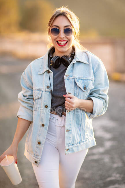 Joyful blond haired woman in stylish outfit and sunglasses walking with beverage and smiling on blurred background — Stock Photo
