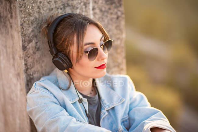 Jovem mulher alegre com óculos de sol em roupa casual na moda sorrindo e olhando para longe no dia ensolarado — Fotografia de Stock