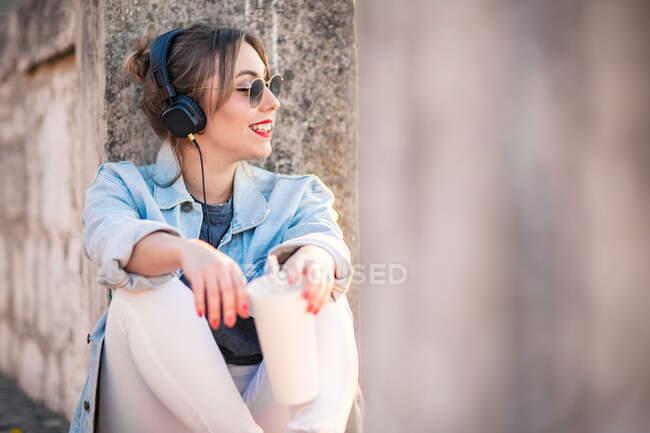 Giovane donna felice in abbigliamento casual con occhiali da sole poggiati su recinzione rocciosa con bevanda e musica d'ascolto con cuffie — Foto stock