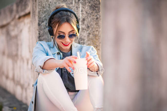 Joven mujer feliz en ropa casual con gafas de sol descansando en la valla rocosa con bebida y escuchar música con auriculares - foto de stock