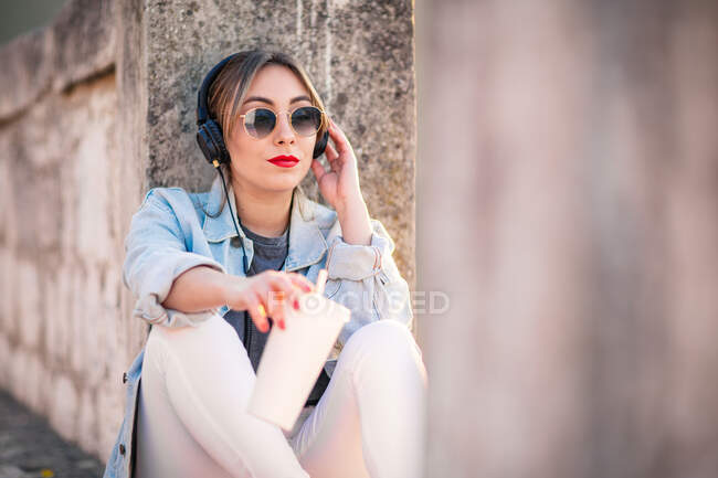 Young woman in casual wear with sunglasses resting on rocky fence with beverage and listening music with headphones — Stock Photo