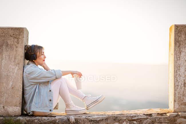 Seitenansicht einer nachdenklichen Dame in Freizeitkleidung, die mit Getränken und Musik über Kopfhörer auf einem felsigen Zaun ruht — Stockfoto