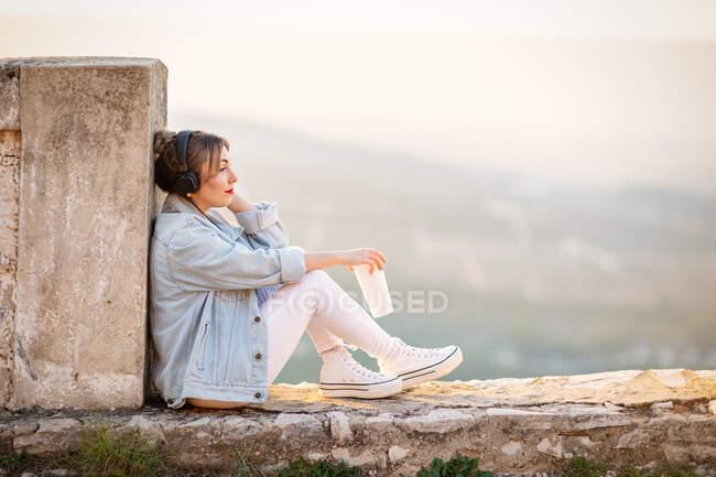 Vista lateral de la dama reflexiva en ropa casual descansando sobre una valla rocosa con bebida y escuchando música con auriculares - foto de stock