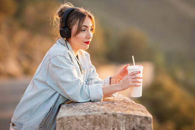 Side view of young lady in trendy jeans jacket with red lips leaning elbows on fence and admiring view with headphones and beverage — Stock Photo