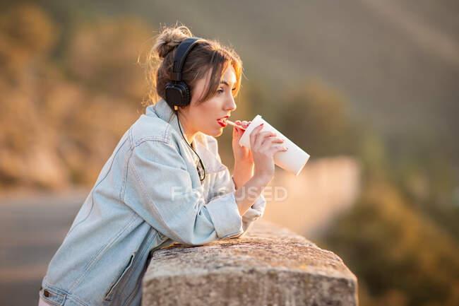 Seitenansicht der jungen Dame in trendiger Jeansjacke mit roten Lippen, die Ellbogen an Zaun lehnen und bewundernde Sicht mit Kopfhörern und Getränken — Stockfoto