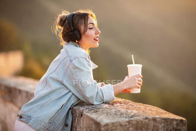 Vista lateral da jovem senhora na jaqueta jeans na moda com lábios vermelhos cotovelos inclinados na cerca e admirando vista com fones de ouvido e bebida — Fotografia de Stock