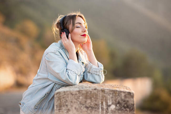 Side view of satisfied young lady in stylish casual wear and red lips leaning elbow on rocky fence with closed eyes while listening music with headphones — Stock Photo