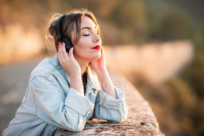 Вид сбоку довольной юной леди в стильной повседневной одежде и красные губы, прислоняющиеся локтем к каменистой ограде с закрытыми глазами, слушая музыку в наушниках — стоковое фото