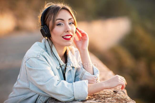 Вид на счастливую улыбающуюся молодую леди в стильной повседневной одежде и красные губы, прислоняющиеся локтем к каменистой ограде, смотрящую в камеру, слушая музыку в наушниках — стоковое фото