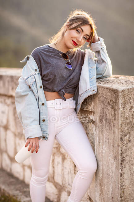 Joyful young woman in trendy casual outfit smiling and looking at camera on sunny day — Stock Photo