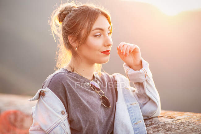 Joyful young woman in trendy casual outfit smiling and looking away on sunny day — Stock Photo