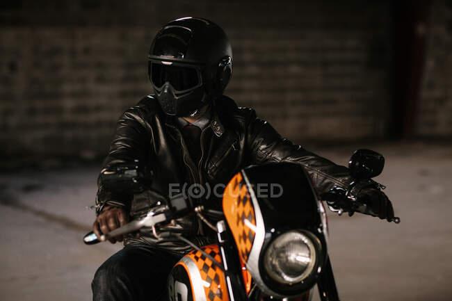 Elegante hombre sentado en su bonita motocicleta dentro de un garaje. - foto de stock